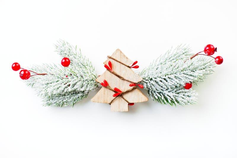 Weihnachtszusammensetzung mit Weihnachtsbaum, grüner Tannenzweig im Schnee und rote Stechpalmenbeeren auf weißem Hintergrund lizenzfreie stockbilder