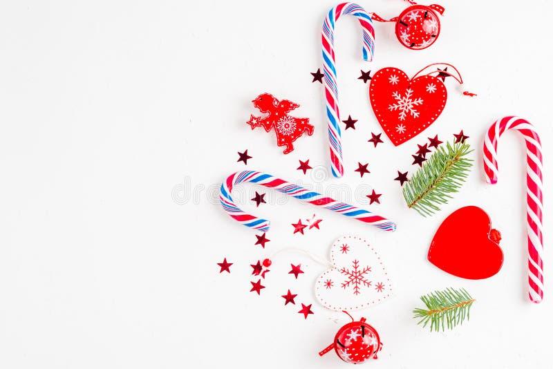 Weihnachtszusammensetzung mit Weihnachtssüßigkeit, Baumasten und Feiertagsverzierung auf weißem Hintergrund Flache Lage, Draufsic stockbild