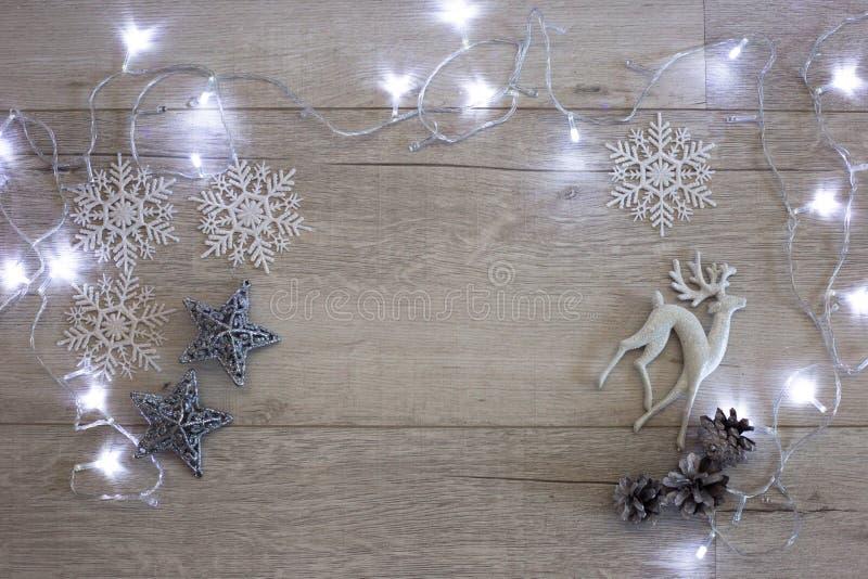 Weihnachtszusammensetzung: Spielzeugrotwild, Schneeflocken, silbernen Sterne und eine Girlande lizenzfreies stockbild