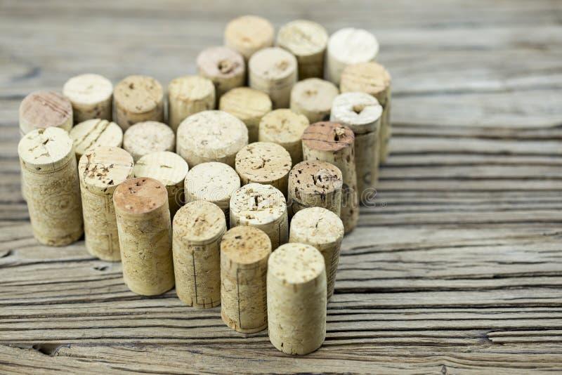Wein bekorkt Form eine Herzform auf der hölzernen Bretthintergrund Valentinstagzusammensetzung lizenzfreie stockbilder