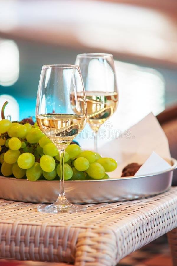 Wein in den Gläsern nahe den Trauben auf einem Behälter auf dem Hintergrund des Pools lizenzfreie stockbilder