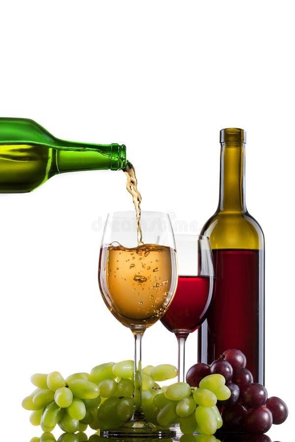 Wein, der in Glas mit Traube und Flaschen gießt lizenzfreie stockbilder