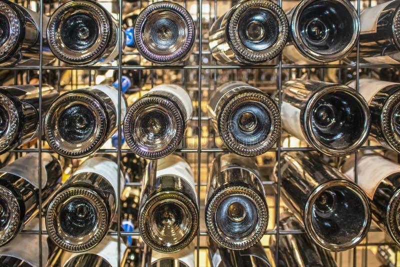 Wein in einem Metallseetang - Ansicht von Unterseiten von Flaschen einer Vielzahl von Marken - Hintergrund des selektiven Fokus lizenzfreies stockbild
