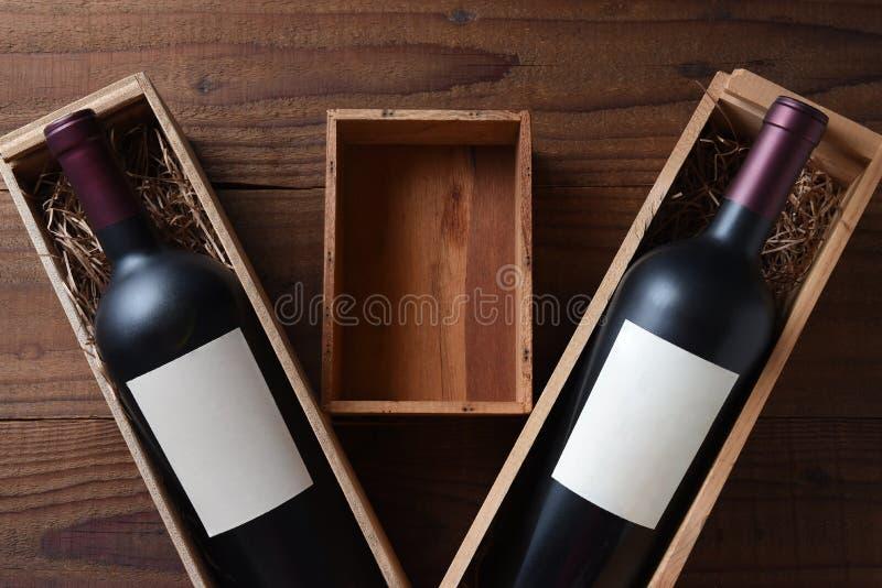 Wein-Stillleben: Zwei hölzerne Weinkästen mit einer Flasche mit leeren Aufklebern Zwischen den Kästen ist ein kleiner leerer Kast stockfoto