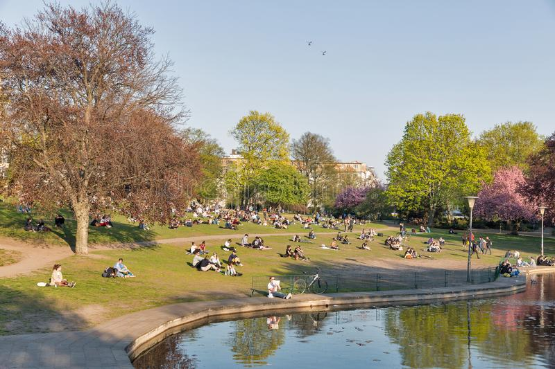 Weinberg park in Berlin, Germany. BERLIN, GERMANY - APRIL 18, 2019: People have a rest near small lake in sunset city Weinberg park at spring. Berlin is the stock images