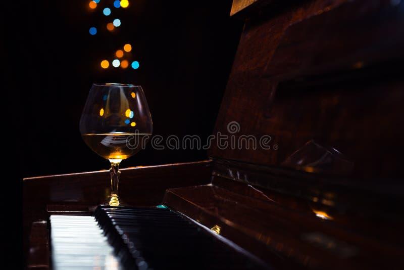 Weinbrand auf einem alten Klavier lizenzfreie stockbilder