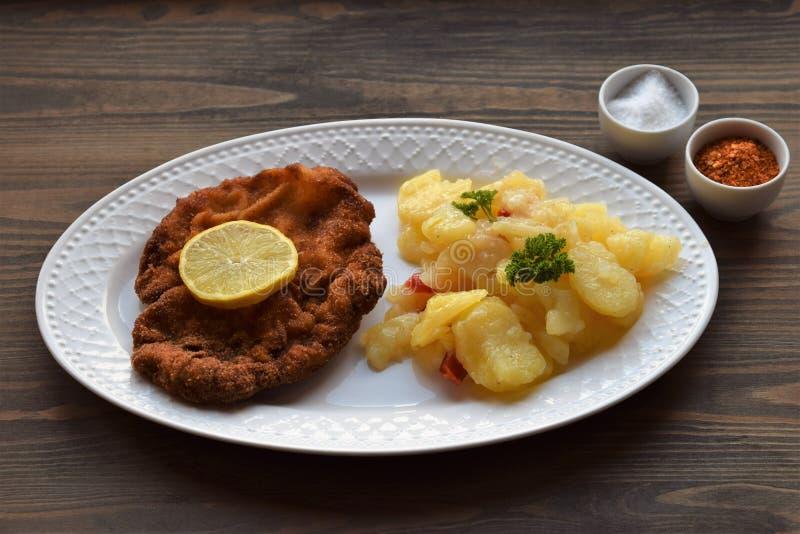 Weinerschnitzel met aardappelsalade op een houten achtergrond stock foto