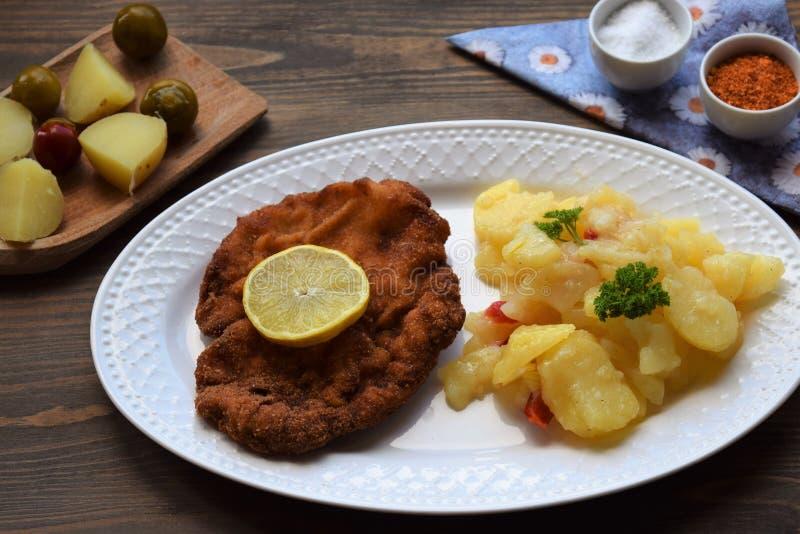 Weinerschnitzel met aardappelsalade op een houten achtergrond stock afbeelding