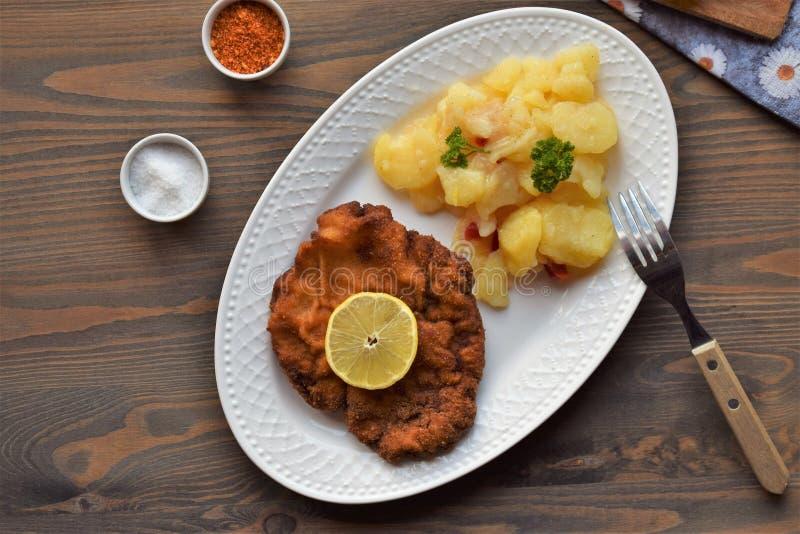 Weinerschnitzel met aardappelsalade op een houten achtergrond royalty-vrije stock fotografie