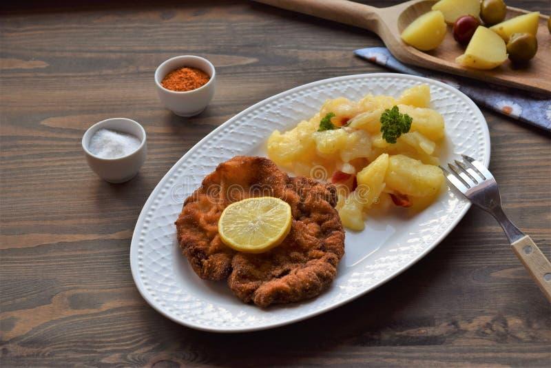 Weinerschnitzel met aardappelsalade op een houten achtergrond royalty-vrije stock foto's