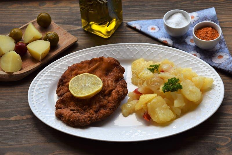 Weinerschnitzel met aardappelsalade op een houten achtergrond royalty-vrije stock afbeelding