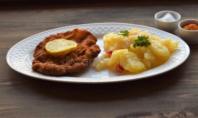 Weinerschnitzel met aardappelsalade op een houten achtergrond royalty-vrije stock foto
