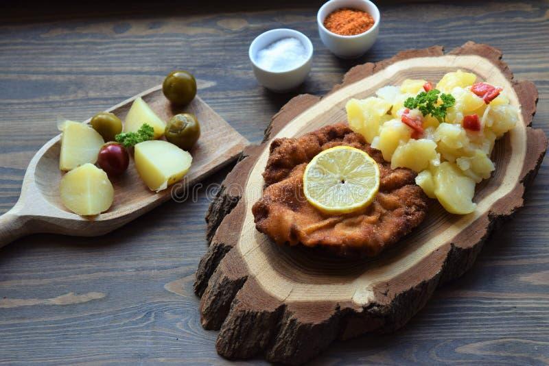 Weinerschnitzel met aardappelsalade op een houten achtergrond stock afbeeldingen
