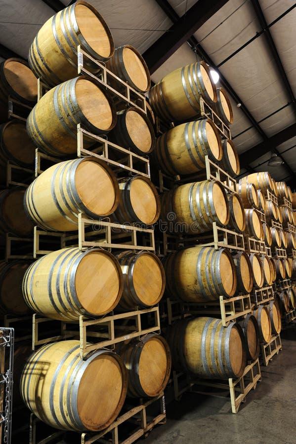 Weinfässer gestapelt in der Weinkellereiseite stockbilder
