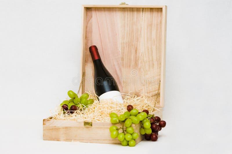 Weinflasche im hölzernen Kasten mit Trauben lizenzfreie stockfotos