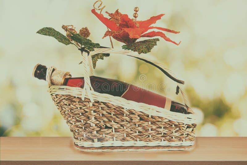 Weinflasche mit leerem Aufkleber auf anwesendem Korb mit gefälschter Blume lizenzfreie stockfotografie