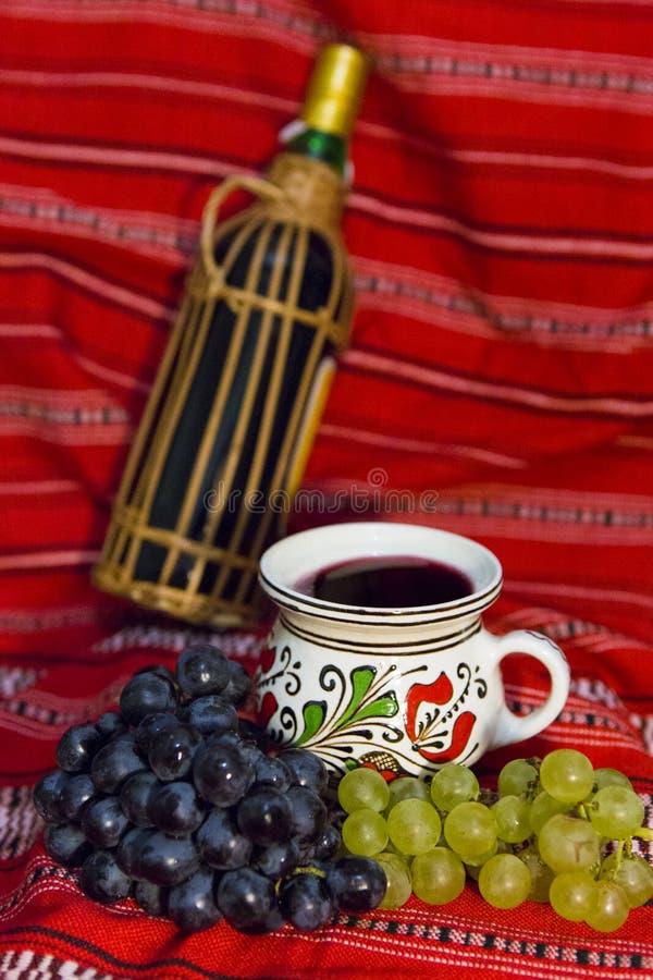 Weinflasche, traditioneller Becher gefüllt mit Rotwein und rote und weiße Trauben auf einem traditionellen rumänischen Teppich lizenzfreie stockfotos