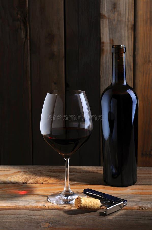 Weinflasche und Weinglas in der Kellereinstellung lizenzfreies stockfoto
