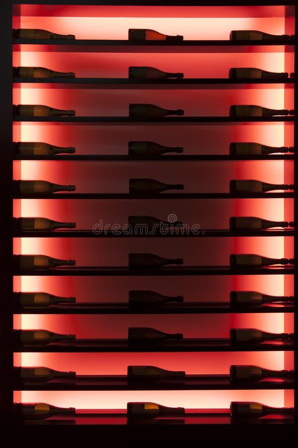 Weinflaschen in einem belichteten Weinkühlraum stockbilder