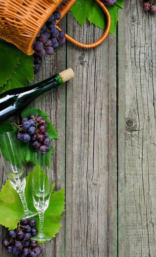 Weinflaschen mit Trauben, Korb, zwei Weingläser auf rustikalem Holz Vertikale Weinherstellung lizenzfreie stockfotos