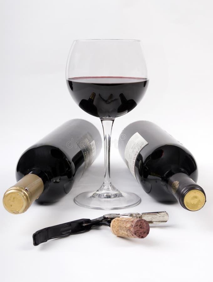 Weinflaschen und ein Glas Rotwein lizenzfreie stockbilder