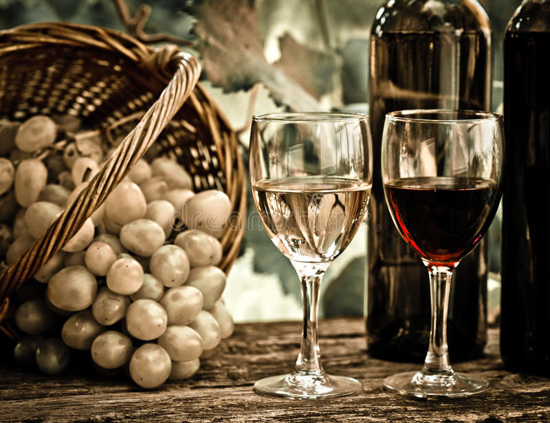 Weinflaschen, zwei Gläser und Trauben im Korb stockbilder