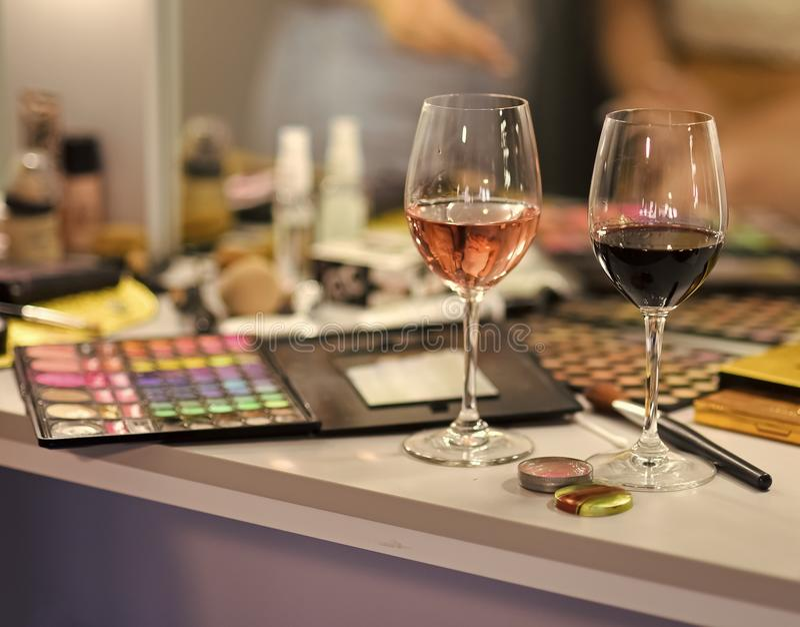 Weingläser auf Tabelle in der Umkleidekabine Maskenbildnerausrüstung, Palette, Kosmetik Frisierkommode im Schönheitssalon visage stockfoto