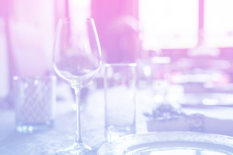 Weinglas an der Feier und speisen Gedeck mit Blumendekorationen auf hellrosa blauem Steigungshintergrund stockbild