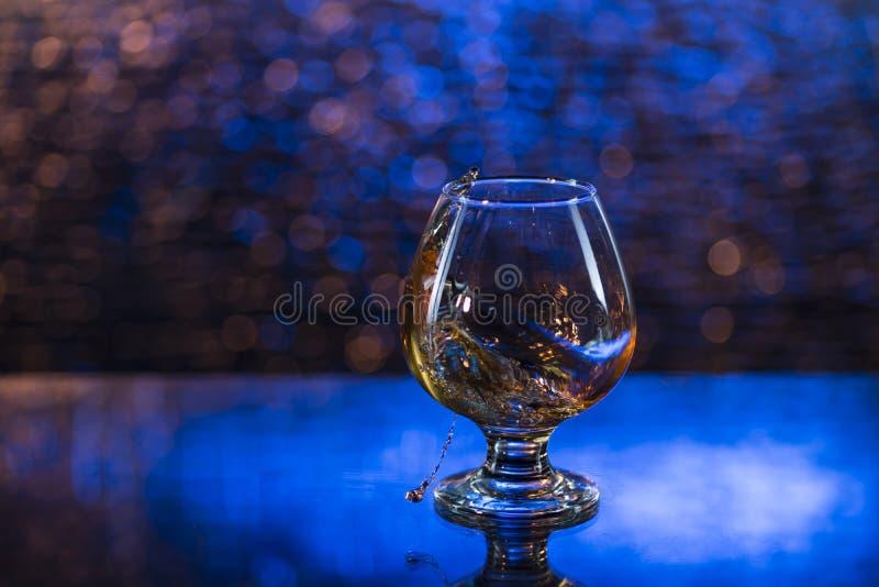Weinglas Kognak und Spritzen auf einem blauen bokeh Hintergrund lizenzfreie stockfotografie