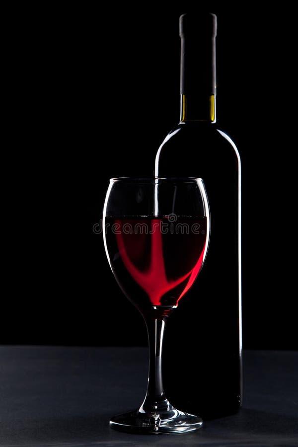 Weinglas und -flasche auf schwarzem Hintergrund stockfotos