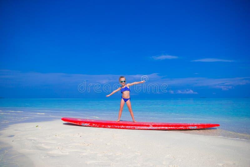 Weinig aanbiddelijk meisje op een surfplank in stock afbeelding