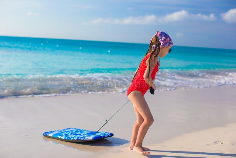 Weinig aanbiddelijk meisje trekt een surfplank op witte kust stock foto
