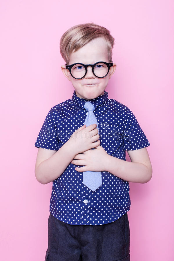 Weinig aanbiddelijke jongen in band en glazen school peuter Manier Studioportret over roze achtergrond royalty-vrije stock fotografie