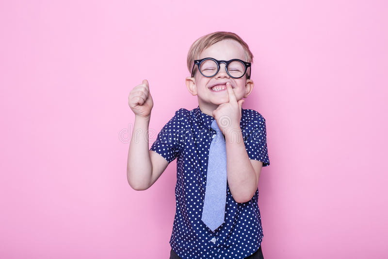 Weinig aanbiddelijke jongen in band en glazen school peuter Manier Studioportret over roze achtergrond stock afbeeldingen