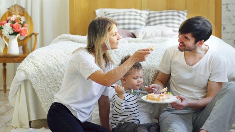 Weinig aanbiddelijke jongen die zijn verjaardag met vader en moeder vieren eet cake in slaapkamer royalty-vrije stock foto