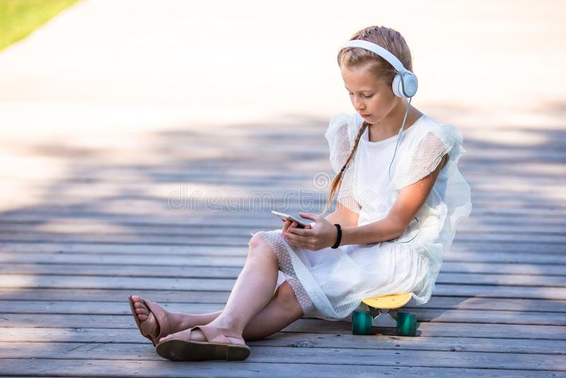 Weinig aanbiddelijke meisje het luisteren muziek in het park royalty-vrije stock afbeeldingen
