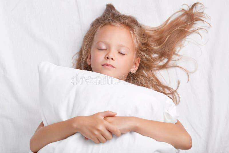 Weinig aantrekkelijke dochter met gesloten ogen, omhelst zacht wit hoofdkussen tijdens slaap, geniet van binnenlandse comfortabel stock foto