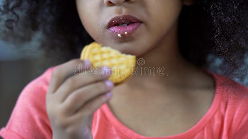 Weinig aardig meisje die zoet koekje, lippen eten kromp met crumbs, ongezond voedsel ineen stock foto