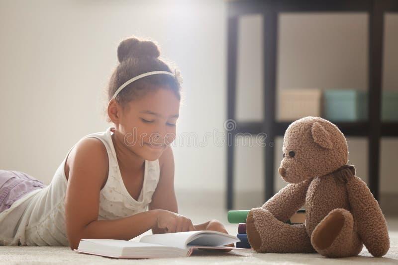 Weinig Afrikaans-Amerikaan boek van de meisjeslezing terwijl thuis het liggen op vloer royalty-vrije stock afbeeldingen