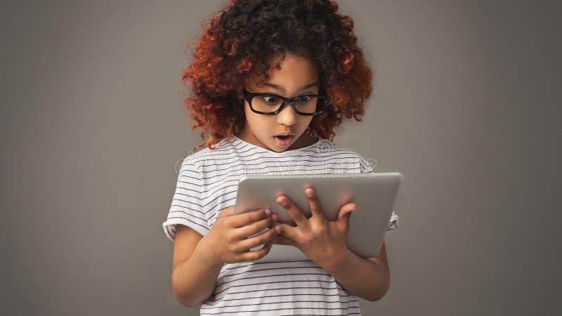 Weinig Afrikaans meisje die digitale tablet, studioschot gebruiken royalty-vrije stock fotografie