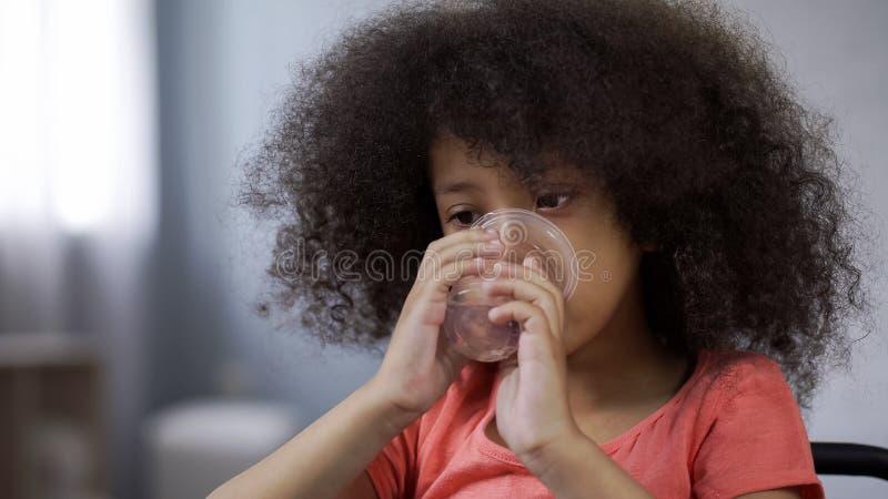 Weinig Afrikaans meisje die nog mineraalwater vloeibaar saldo in lichaam, close-up drinken royalty-vrije stock afbeelding
