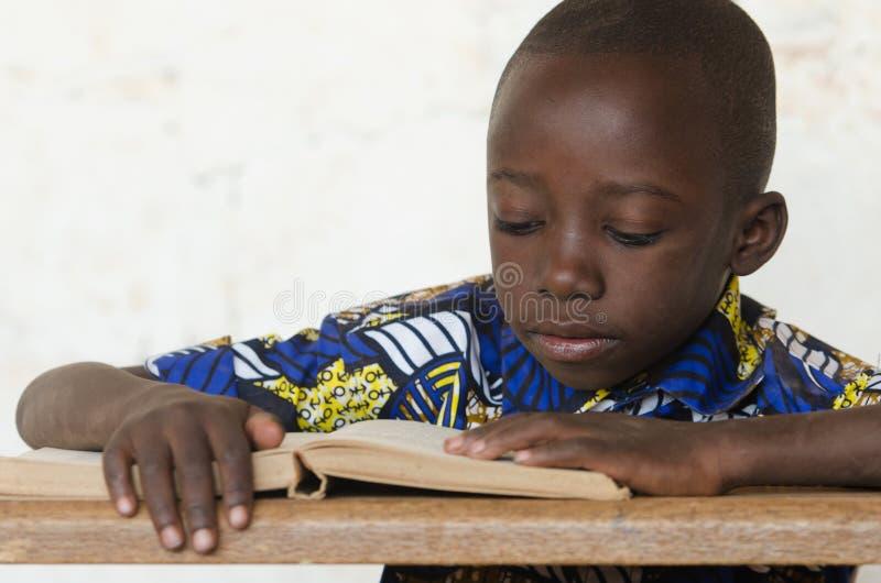 Weinig Afrikaanse Jongen die Groot Boek lezen op School met exemplaarruimte stock foto