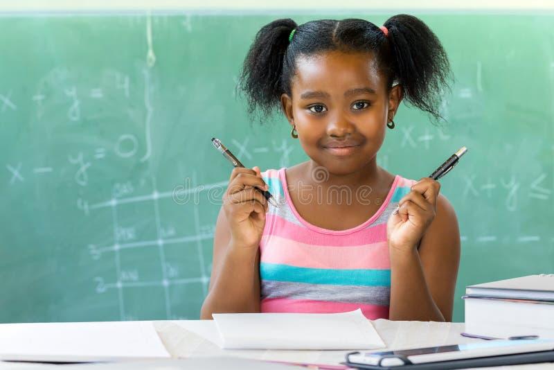 Weinig Afrikaanse meisjeszitting bij bureau in klaslokaal met bord stock foto