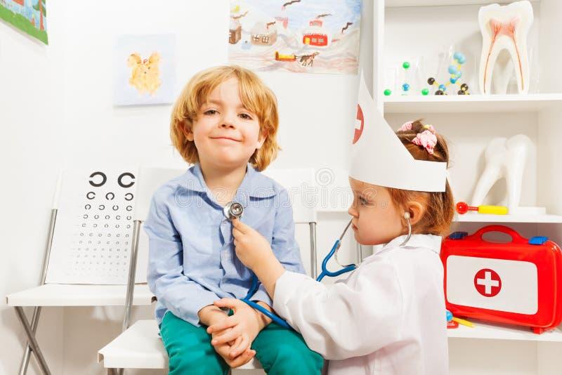 Weinig arts die jongen met stethoscoop onderzoeken royalty-vrije stock afbeelding