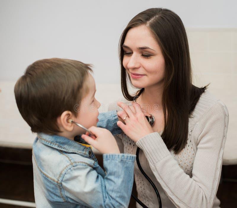 Weinig artsenjongen die met zijn moeder spelen die aan haar borst luisteren die stethoscoop met behulp van stock foto