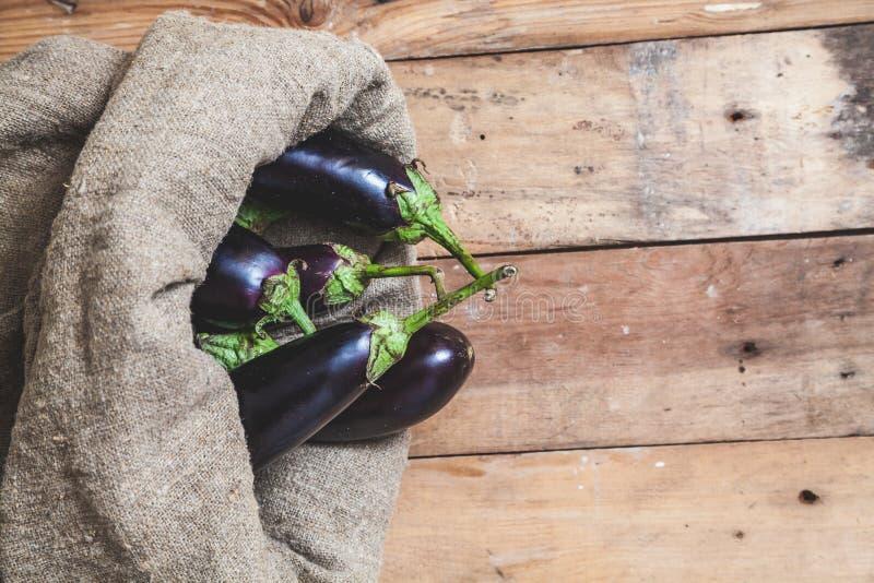 Weinig aubergines worden gezien in zak op houten raad stock fotografie