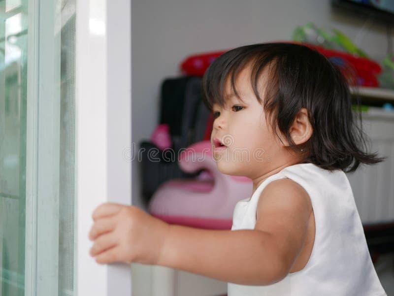 Weinig Aziatisch babymeisje/dichte schuifdeur die leren zelf te sluiten stock fotografie