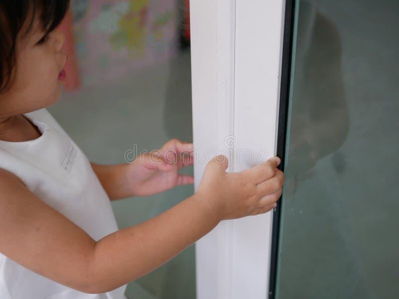 Weinig Aziatisch babymeisje/dichte schuifdeur die leren zelf te sluiten royalty-vrije stock afbeeldingen