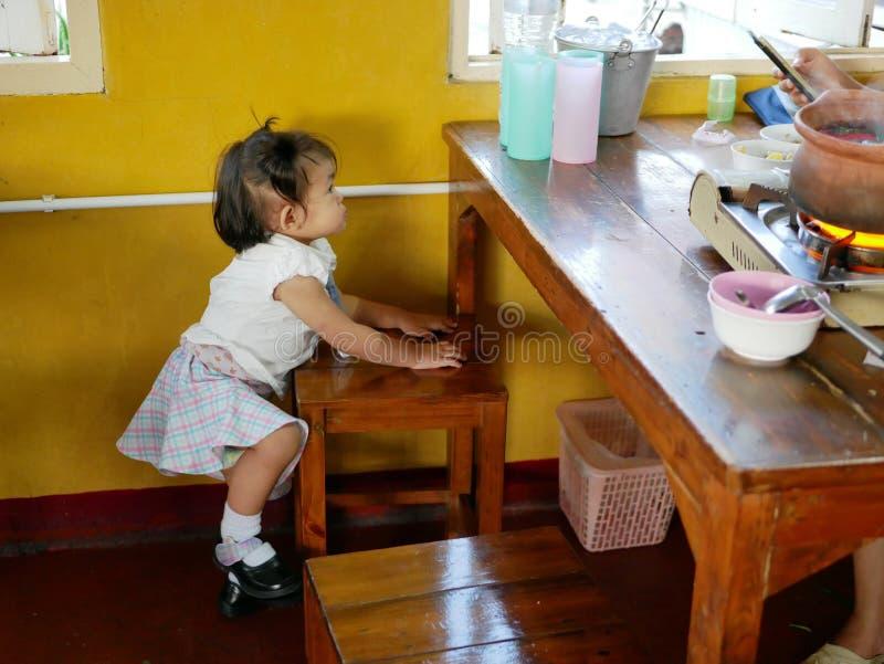 Weinig Aziatisch babymeisje die een houten stoel beklimmen om kleurrijke plastic koppen te krijgen stock foto