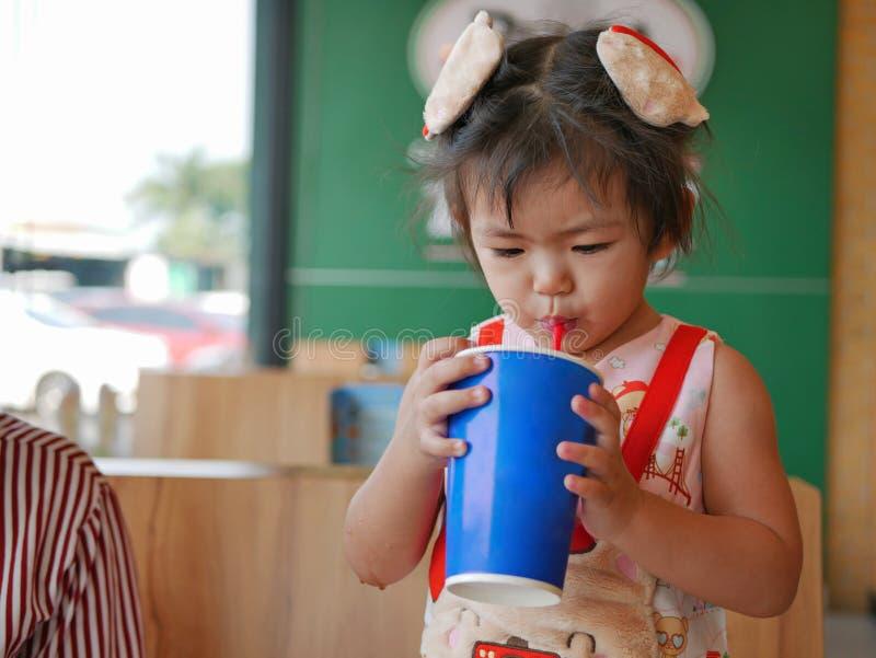 Weinig Aziatisch babymeisje die grote kop van sprankelende frisdrank zelf in een restaurant drinken royalty-vrije stock foto